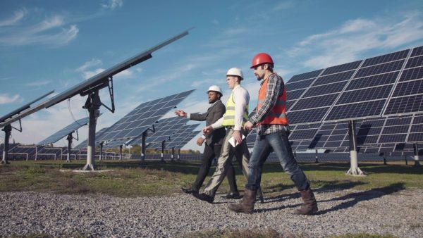 three professionals in solar power station.